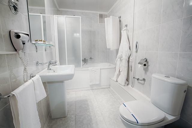Interior design of a hotel bathroom. Hotel restroom interior design. Washbasins, sink, toilet, shower cabin. Clean public bathroom in hotel, disinfected. Contemporary interior design. Modern bathroom.